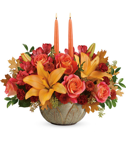"Artistic Glow Orange Lily Fall Centerpiece from Enchanted Florist. This glowing arrangement includes orange roses, peach asiatic lilies, red alstroemeria, bronze button spray chrysanthemums, burgundy cushion spray chrysanthemums, seeded eucalyptus, huckleberry, yellow transparent oak leaves, and two peach candles. Delivered in an Artisanal Autumn Bowl. Approximately 18"" W x 16"" H SKU T19T105"