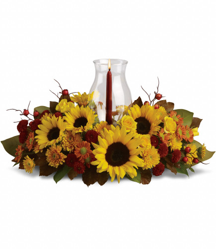 "Sunflower Thanksgiving Centerpiece with Globe from Enchanted Florist. Along with brilliant sunflowers, you'll find yellow spray roses, bronze and rust chrysanthemums, red berries, magnolia leaves and of course an elegant tapered candle inside a hurricane vase. Approximately 21"" W x 14"" H SKU RM231"