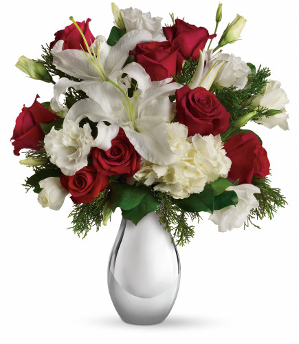 "Silver Noel Greetings Christmas Bouquet from Enchanted Florist. Our lovely holiday bouquet includes a white hydrangea, red roses, fragrant white oriental lilies and white lisianthus accented with flat cedar. Approximately 15"" W x 17"" H SKU RM258"