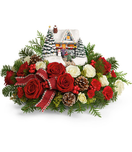 "Thomas Kinkade's Homecoming Hero Christmas Bouquet from Enchanted Florist. This arrangement includes red roses, miniature white roses, miniature red carnations, seeded eucalyptus, noble fir, and flat cedar. Delivered with Teleflora's Thomas Kinkade's Hero's Welcome Keepsake. Approximately 18"" W x 10"" H SKU T20X205"