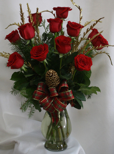 "Santa's Premium Christmas Dozen Red Roses from Enchanted Florist. Twelve beautiful red rose blossoms mix with Christmas greenery and gold accents including a golden pinecone with the beautiful plaid bow. Approximately 16"" W x 26"" H   SKU RM265"