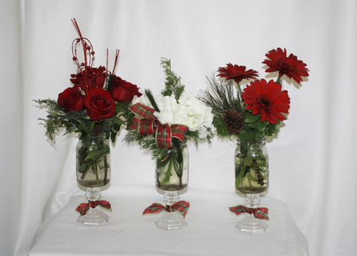 "Christmas Bouquet Trio of Red and White Flowers from Enchanted Florist. This unique tablescape style group of bouquets includes three different arrangements in our exclusive up-cycled mason jars for a rustic Christmas feel. The first vase includes red roses, the second white hydrangeas, and the third red gerbera daisies. All include Christams greenery and accents like the picture. Approximately 10"" W x 15"" H   SKU RM264"