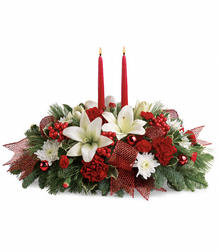 """Magical Yuletide Christmas Centerpiece with Candles from Enchanted Florist Pasadena TX. This stunning centerpiece features red carnations, white oriental lilies, red mini pixie carnations, white cushions, variegated holly, noble fir, flat cedar, white pine, red berries, red ornament balls, red ribbon, and red taper candles. Approximately 22"""" W x 15"""" H.  SKU RM270"""
