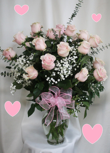 """Two Dozen Light Pink Roses for Valentine's Day by Enchanted Florist Pasadena TX. This show stopping bouquets of our lush and romantic light pink roses comes complete with baby's breath, greens and a bow and is hand arranged by our premier floral designers. Approximately 26""""H x 16""""W   SKU RM956"""
