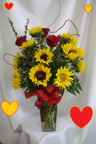 "Sunflower and Red Rose Valentine's Day Bouquet from Enchanted Florist. When you're looking for something a little different for Valentine's Day! Sunflowers are easily one of most popular flowers year round so we have paired them here with the classic Valentine's flower... the red rose. It is accented with various greens, curly willow, and a lady bug for a hidden surprise. Approximately 26""H x 22""W. SKU RM936"