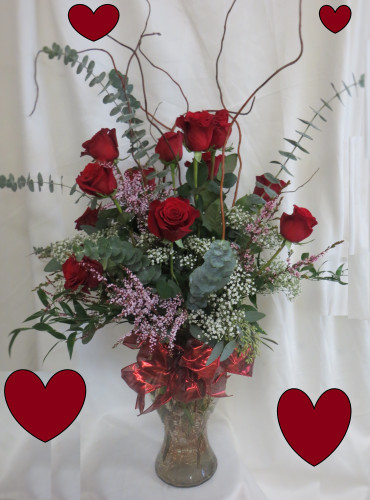 """The Show Stopper One Dozen Red Roses for Valentine's Day from Enchanted Florist.  Our beautiful long stem red roses from Ecuador are hand delivered in an upgraded curvy Marilyn Monroe vase using premium foliages like eucalyptus and italian ruscus, curly willow, and topped off with two types of filler, baby's breath and pink wax flower. Approximately 36""""H x 22""""W SKU RM966"""
