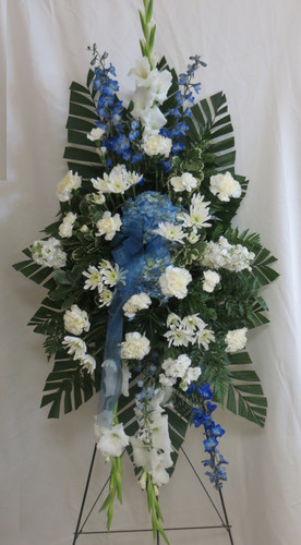 "Sapphire Blue & White Funeral Spray from Enchanted Florist.  Our beautiful blue and white sympathy standing spray of flowers.  It includes blue delphinium, blue hydrangeas, white carnations and white stock with accent foliages. Approximately 70""H x 36""W size not including stand. SKU RM547"
