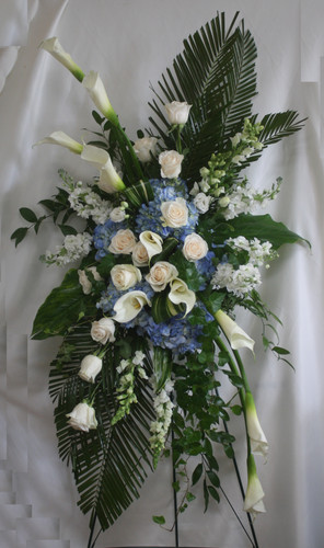 "Galaxy Wide Blue and White Funeral Flowers Spray from Enchanted Florist. One of our largest sprays in blue and whites, our custom spray includes large white calla lilies, one dozen white roses. blue hydrangeas, white stock, white snapdragons, and lots of green foliage to set the design off. Approximately 70""H x 40""W (size not including stand) SKU RM548"