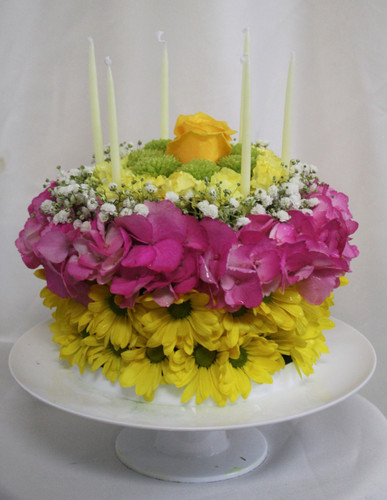 "Happy Birthday Cake in Yellow from Enchanted Florist - This beautiful birthday cake of yellow flowers will light up any birthday girl's face, with out adding any pounds! Includes yellow daisies, hydrangeas, baby's breath, pixie carnations, and a rose on a cake stand. Yes! Cake stand and candles are included. Approximately 11""W x 8""H. For local delivery only. SKU RM135"