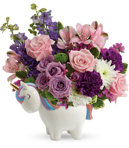 """Magical Mood Unicorn in Purple Enchanted Florist. This magical gift features lavender spray roses, pink alstroemeria, fuchsia carnations, purple larkspur, white cushion spray chrysanthemums, green button spray chrysanthemums, raspberry statice, and variegated pitt. Delivered in a Charmed Unicorn Keepsake. Approximately 12"""" W x 13"""" H SKU RM133"""