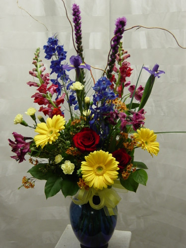 "Bold Blue Beauty Bouquet with Yellow Gerbera Daisies from Enchanted Florist Pasadena TX. This beautiful bouquet includes yellow gerbera daisies, iris, blue delphinium, purple liatris, pink snapdragons, and so much more. Approximately 30""H x 22""W  For local delivery only. SKU RM102"