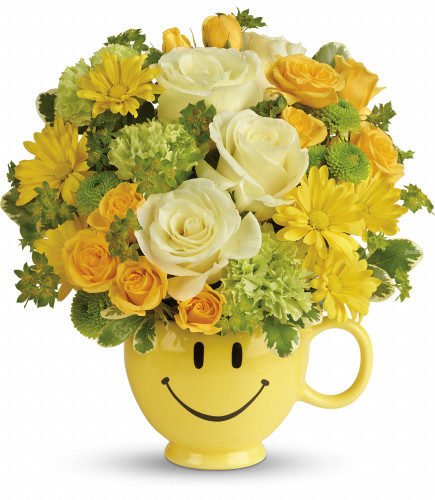 """You Make Me Smile Mug with Yellow Flowers from Enchanted Florist. This cheerful bouquet includes light yellow roses, yellow spray roses, green carnations, green button spray chrysanthemums, yellow daisy spray chrysanthemums, bupleurum and variegated pittosporum. Delivered in a Be Happy mug. Approximately 11"""" W x 11 1/2"""". SKU RM103"""