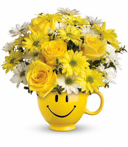 """Just Be Happy with Yellow Roses from Enchanted Florist. Yellow roses and daisies along with white daisies and oregonia are delivered in the one and only Be Happy® mug. Approximately 11"""" W x 11"""" H. SKU RM104"""