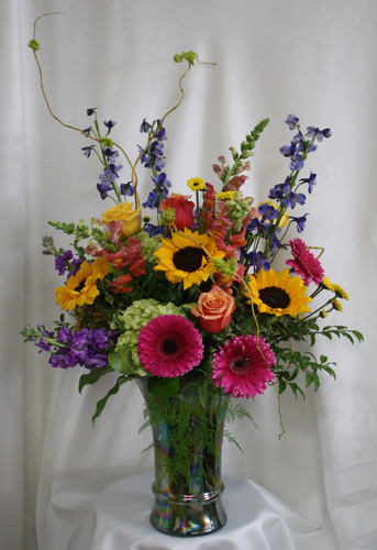 "Fire and Frenzy Bright Colored Bouquet from Enchanted Florist Pasadena TX. This beautiful bouquet includes yellow sunflowers, gerbera daisies, green hydrangeas, blue delphinium, snapdragons, purple stock, orange roses, yellow roses, and yellow daises and is accented with the perfect greenery touches. Approximately 30""H x 24""W  For local delivery only. SKU RM108"