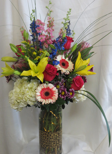 "Fun and Frisky Yellow Lily Bouquet from Enchanted Florist Pasadena TX.  This beautiful bouquet includes yellow Asiatic lilies, pink gerbera daisies, white hydrangeas, blue delphinium, pink larkspur, red roses, purple daisies and is accented with the perfect greenery touches. Approximately 34""H x 22""W  For local delivery only. SKU RM109"
