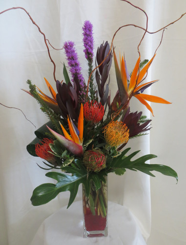 """Eden Always Bird of Paradise Bouquet from Enchanted Florist Pasadena TX. This tropical bouquet includes birds of paradise, purple liatris, protea, safari sunset and is accented with the perfect greenery touches. Approximately 26""""H x 16""""W  For local delivery only. SKU RM114"""