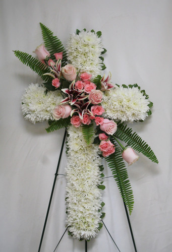 "Pink Rose and Stargazer Cross of Sympathy Flowers from Enchanted Florist. Stunning funeral flowers such as pink roses, pink spray roses, and pink stargazer lilies are arranged on this floral cross that is covered in white mum flowers is full of love and devotion, arriving on a wire funeral easel. Approximately 22"" W x 34"" H (Dimensions do not include easel) SKU RM552"