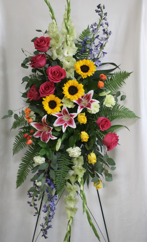 """Thoughtful Memories Mixed Spray of Funeral Flowers from Enchanted Florist. This beautiful spray is designed with stargazer lilies, green gladiolas, blue delphinium, sunflowers, shot pink and yellow roses and green carnations, and lots of green foliage to set the design off. Approximately 60""""H x 30""""W (size not including stand) SKU RM556"""