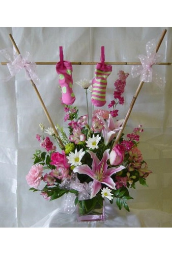 Baby Girl Clothesline Flower Bouquet with Socks by Enchanted Florist. The adorable bouquet includes pink roses, stargazer lilies, pink larkspur, & white daisies in a pink & white theme. SKU RM320