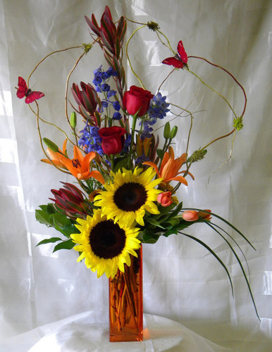 "Bursting with Butterflies Red Rose and Orange Lily Bouquet from Enchanted Florist. Butterflies are bursting out of this beautiful arrangement. A bright bouquet of flowers bursting with happy butterflies, sunflowers, two red roses, orange lilies, blue delphinium, and other flowers.  Approximately size 34""H x 16""W. SKU RM119"