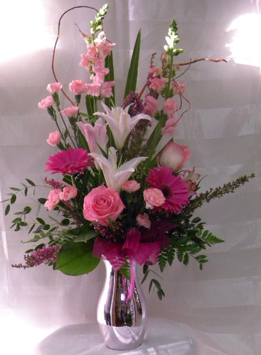 """Hot Pink Perfection Pink Rose Arrangement from Enchanted Florist. This bouquet is just perfection in Pink!! Shades of pink flowers including lilies, gerberas, roses, snapdragons, and carnations arranged in a silver vase. For local delivery only. Same-day delivery available.  Approximately 28""""H x 11""""W. SKU RM123"""