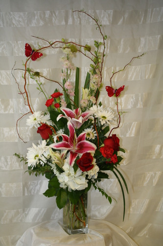 """The Wild Butterflies Bouquet in Red from Enchanted Florist is a perfect mix of fresh flowers and wild dancing butterflies. Red roses, white hydrangeas, star gazer lilies, white daisies, red pixie carnations and curly willow branches with flittering butterflies on the branches. Approximately 34""""H x 13""""W. SKU RM125"""