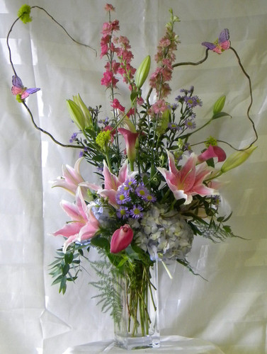 "Wild Butterflies Arrangement with Blue Hydrangeas from Enchanted Florist is a perfect mix of the best flowers spring has to offer. Mini calla lilies, hydrangeas, fragrant stargazer lilies, larkspur and of course the wild dancing butterflies. Arrives in a clear vase expertly designed by our floral designers. Approximately 36""H x 12""W. For local delivery only. SKU RM107"