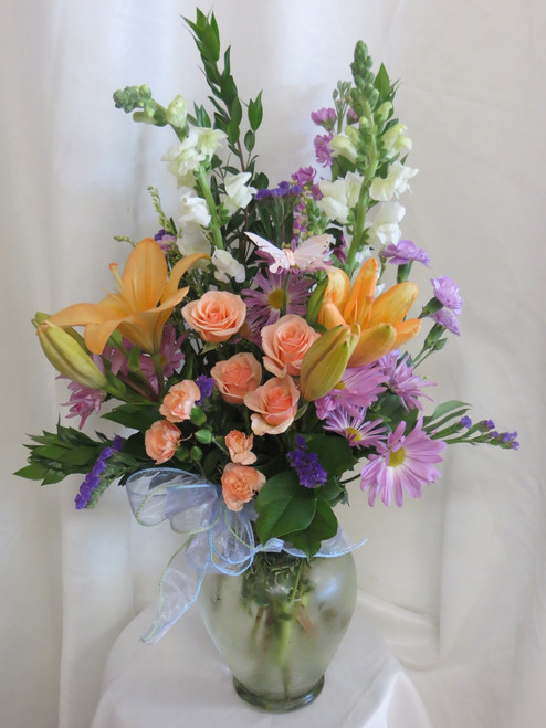 """In the Moonlight Orange Lily and Rose Bouquet by Enchanted Florist Pasadena is a beautiful mixed flower bouquet that will cheer anyone up. It includes orange lilies, white snapdragons, peach spray roses, purple stock and purple daisies all presented in a clear glass vase. Approximately 27""""H x 18""""W SKU RM122"""
