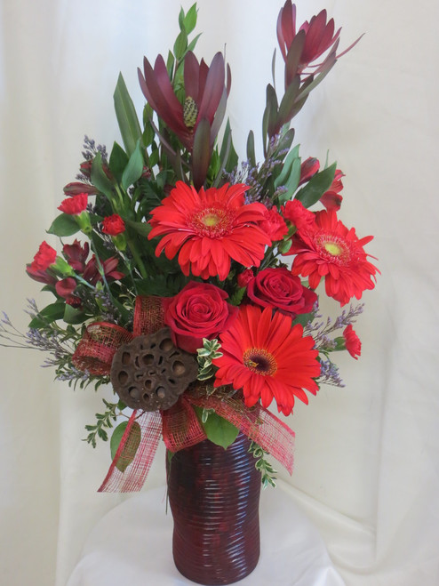 """Our Visions in Red Gerbera and Rose Bouquet from Enchanted Florist will absolutely make a statement for any birthday. This bright red arrangement includes gerberas, roses, safari sunset, pixie carnations, and a lotus pod. So striking! Approximately 24""""H x 16""""W   SKU RM124"""