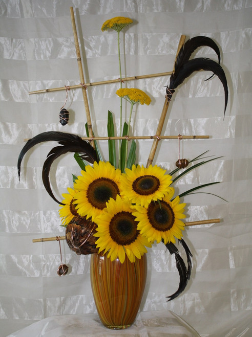 """Bellini Sunflower Bouquet with Bamboo Trellis by Enchanted Florist Pasadena - This contemporary and stylish arrangement is sure to catch anyone's eye. A unique masterpiece accented with stones, wire, and feathers. Includes sunflowers and a bamboo trellis. Approximately 30""""H x 16W.  SKU RM216"""