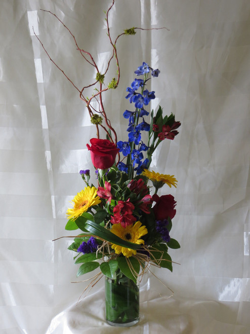 """Beautiful Blue Bella and Red Rose Bouquet by Enchanted Florist- Try something different. Vertical designs give the arrangement height and style. This beautiful bouquet includes red roses, yellow gerberas, blue delphinium and more. Approximately 28""""H x 10""""W   SKU RM139"""