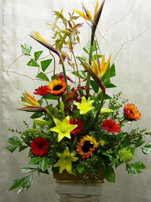 Life's Celebration Funeral Arrangement by Enchanted Florist TX - bright and beautiful funeral flowers arranged in a funeral urn and includes tropical birds of paradise, bright yellow lilies, sunflowers, and gerbera daisies. Daily delivery to Houston funeral homes and churches for a celebration of life flowers arrangement. RM507