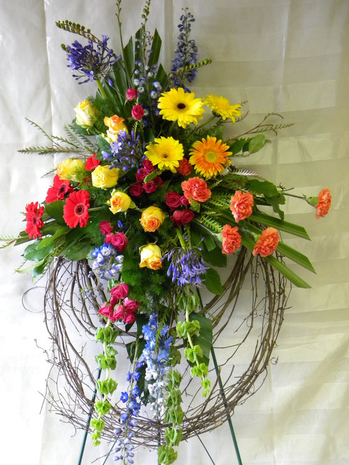 """Eternal Sunshine Grapevine Sympathy Wreath from Enchanted Florist - This bright and colorful floral grapevine wreath will express your compassion to all in attendance. Our funeral wreath includes bright yellow roses, red gerbera daisies, blue delphinium, and more. A unique funeral option for a dearly loved family member.  Approximately 32""""W x 54""""H SKU RM510"""