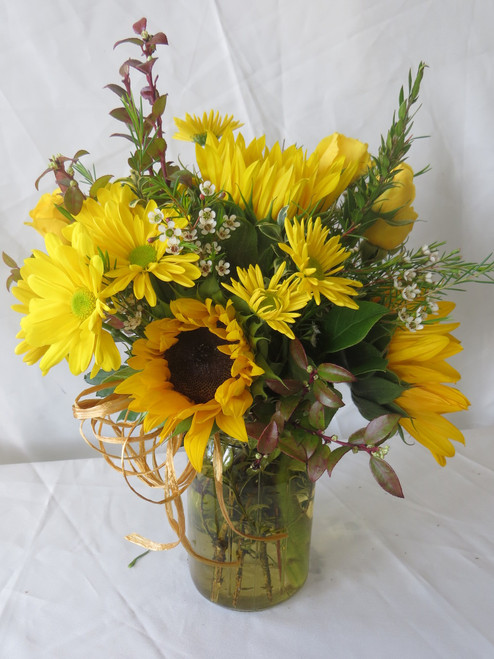 """Sunnyside Fall Sunflowers in Mason Jar by Enchanted Florist Pasadena TX. A lovely country style bouquet of medium sized sunflowers, yellow roses and yellow daisy flowers with delicate wax flowers in a yellow mason jar with raffia bow. A delightful gift! Approximately 10""""H x 8""""W.   SKU RM236"""