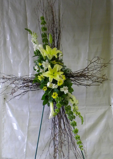 Lovely Birch Sympathy Cross by Enchanted Florist. This birch cross includes yellow lilies, white snaps, and yellow daisies and more for this sympathy floral delivery to funeral homes in Pearland TX. RM524