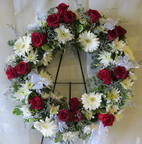 """Divine Sympathy Red Rose & White Flowers Funeral Wreath by Enchanted Florist Pasadena TX. Simply divine, red and white flowers together classically designed in a funeral wreath. Flowers include traditional red roses along with white gerbera daisies and sheer white bows placed together are a great way to remember a loved one. Approx 22""""W 22""""H.   SKU RM526"""