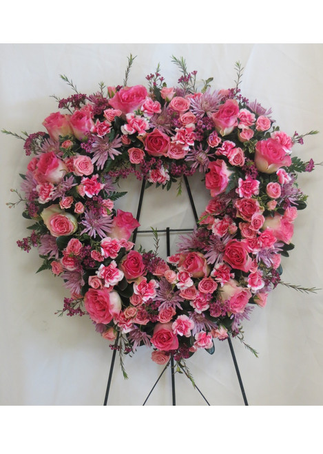 With An Open Heart Pink Rose Funeral Flowers by Enchanted Florist Pasadena TX. A perfectly pink display of all pink and lavender flowers including Malibu pink roses, pink spray roses, lavender daisies and light pink pixies designed into a heart shaped sympathy bouquet. RM534