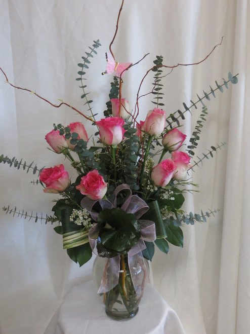 Fly Me Away Pink Dozen Roses by Enchanted Florist Pasadena TX. Our premium Ecuadorian malibu roses in an upgraded vase with curly willow, butterfly, and exotic foliages. Malibu is a special bi-colored rose appearing with hot pink tips along crème colored rose petals. RM364