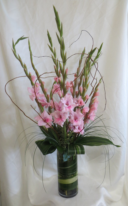 Gracious Gladiola Flower Arrangement by Enchanted Florist Pasadena TX. Vase of all pink gladiolas in a contemporary styled vase with curly willow and tropical foliage accents. RM538