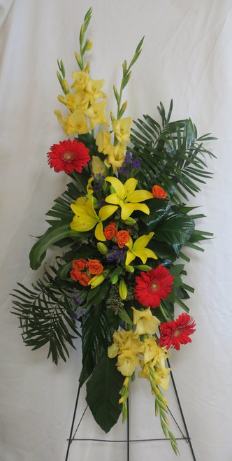 """Sunset Tribute Yellow Funeral Spray of Flowers by Enchanted Florist Pasadena TX. Funeral flowers include yellow gladiolas, yellow lilies, orange gerbera daisies, orange spray roses and exotic green foliages. Arrives hand delivered by our flower professionals on a wire sympathy easel. Approximately 54""""H x 28""""W.   SKU RM541"""