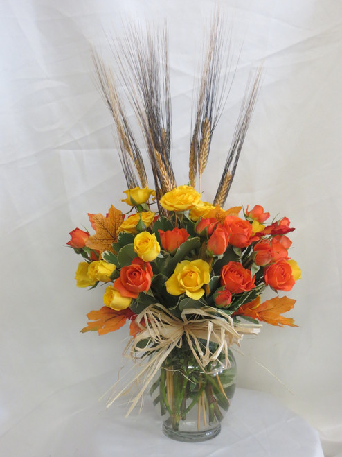 Fall Simply Spray Rose Bouquet by Enchanted Florist Pasadena TX. Our fall bouquet of yellow and orange spray roses in a clear vase with wheat accents and fall leaves perfect for a side table or desk. We offer same day delivery on fall flowers for delivery in Pasadena TX and surrounding areas. RM206