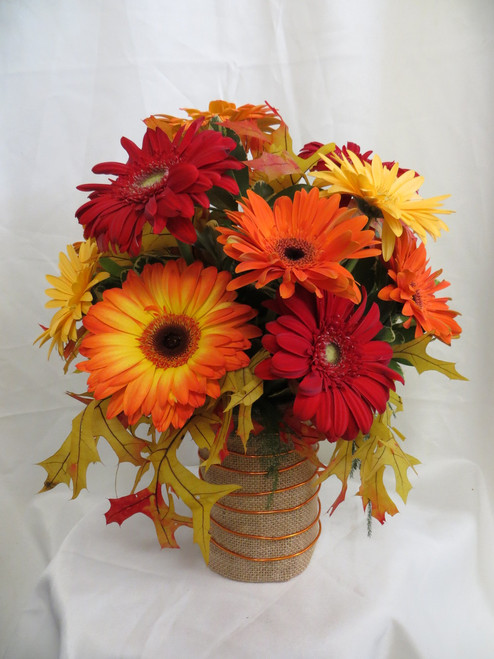 """Autumn Magic Gerbera Daisy Bouquet by Enchanted Florist Pasadena TX. This lovely all fall gerbera daisy bouquet includes a mixture of fall colored gerbera daisies of red, yellow, and oranges arranged in a burlap vase accented with orange wire and fall leaves. Approximately 13""""H x 10""""W. SKU RM207"""