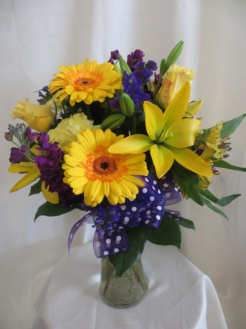 Our beautiful Lush Lavender & Yellow Gerbera Flower Bouquet fills a room with happiness. This bright yellow and purple bouquet of flowers includes yellow roses, lilies, and gerberas with purple stock and statice.  A beautiful and happy bouquet for delivery in Clear Lake, TX.  RM167