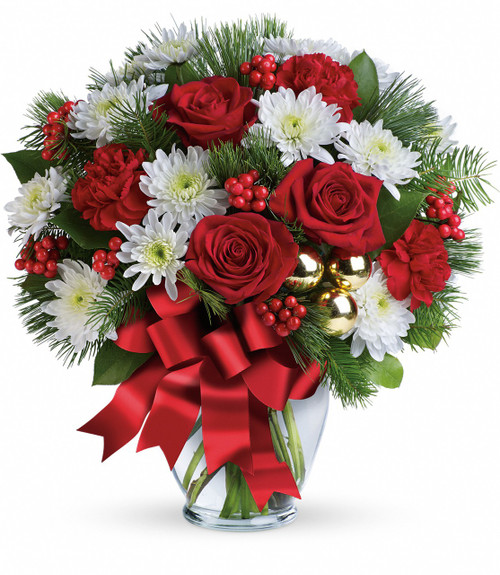 """Merry Beautiful Red Rose Christmas Bouquet from Enchanted Florist. This festive mix includes red roses, white cushions, red carnations, white pine, douglas fir, lemon leaf, red berries and gold ornament balls. Delivered in a glass ginger vase adorned with red ribbon. Approximately 16"""" W x 16"""" H.   SKU RM260"""