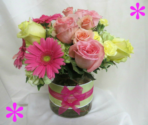 Fashionista Mothers Day Flowers by Enchanted Florist Pasadena TX is a fun and flirty bouquet of pink roses, pink gerbera daisies, yellow roses and green hydrangeas in a contemporary cylinder with a fun ribbon treatment. RM802