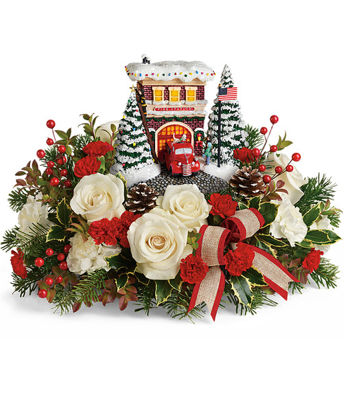 The Teleflora Thomas Kinkade 2019 arrangement, Thomas Kinkade's Hero's Holiday Bouquet. You're sure to be a holiday hero when you send this lush Christmas bouquet! It's arranged around a hand-painted, Thomas Kinkade fire station keepsake that lights up with bright holiday cheer! T19X205