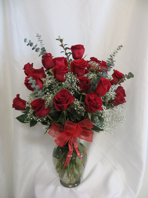 """Love and Devotion 2 Dozen Red Roses by Enchanted Florist Pasadena TX. This show stopping bouquets of our classic red Ecuadorian roses comes complete with greens, baby's breath and a bow and is hand arranged by our premier floral designers. Bouquet size is approximately 26""""H x 16""""W SKU RM371"""