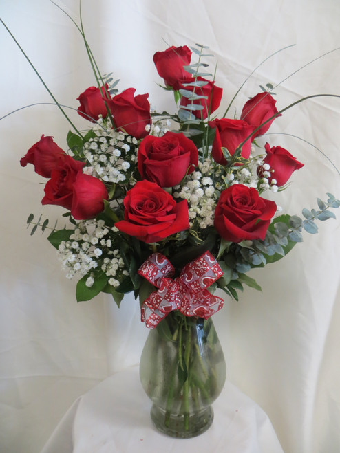 """Deluxe One Dozen Red Roses Bouquet by Enchanted Florist are our most popular style of red roses for delivery. This is our most popular and best value for one dozen red roses. The freshest premium red roses will be hand designed in our upgraded Bella vase, with popular baby's breath, and upgraded premium greenery. Our flower shop offers Houston delivery. One dozen deluxe red roses bouquet is approximately 18""""W x 22""""H  SKU RM375"""