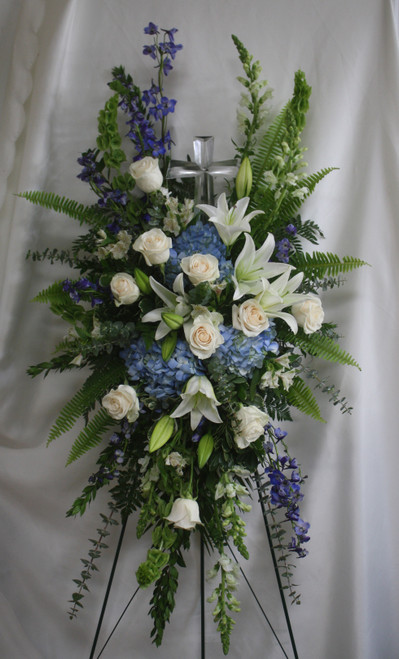 Large Crystal Cross Standing Spray from Enchanted Florist. This special spray includes blue hydrangea, white roses, white oriental lilies, white alstroemeria, bells of Ireland, blue delphinium, white snapdragons, eucalyptus, and and assorted greenery foliages. Delivered on a wire easel with a Large Crystal Cross Keepsake. SKU 562