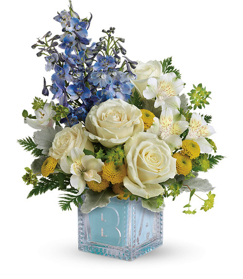Welcome Baby Boy Crystal Block Arrangement by Enchanted Florist. This baby boy crystal block arrangement includes white roses, white alstroemeria, yellow button mums, and blue delphinium are arranged with various fillers and assorted greenery. Hand delivered in our exclusive baby boy crystal block.  RM308